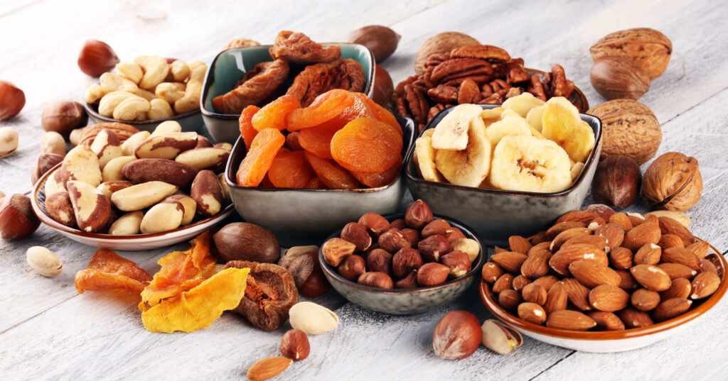dried fruits and assorted nuts composition on rustic table.